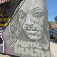 Le visage d'une femme est peint en noir et blanc. On peut lire les mots Santé mentale en anglais.