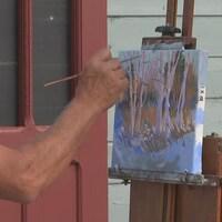 Un artiste peint une toile sur un chevalet.