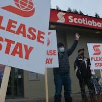 Des gens tiennent des pancartes devant une Banque Scotia.