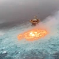 Une image en contre-plongée prise d'un avion montre un trou de flammes au milieu de l'océan, près d'une plateforme de forage. Des bateaux tentent de l'éteindre.