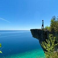 Un rocher surplombe la mer, une femme regarde a l'horizon, l'eau est claire et il y a un peu de verdure.