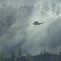 Un hélicoptère au dessus d'un feu de forêt.