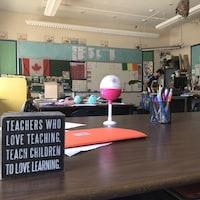 Une table dans une classe avec des objets dessus et un enseignant à son bureau.