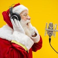Un homme portant un costume de père Noël chante devant un micro de style studio.