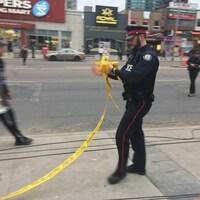 Un policier ramasse les rubans jaunes qui délimitaient le périmètre de sécurité sur la rue Yonge.