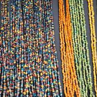 Des rangs de petites perles multicolores sur un étalage.