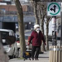 Une personne âgée portant un masque et tirant un porte-sac marche sur un trottoir à Montréal.
