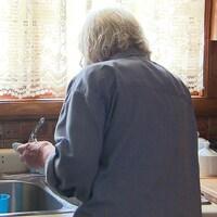 Une femme âgée lave de la vaisselle dans un lavabo.