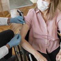 Une personne en chaise roulante reçoit un vaccin.