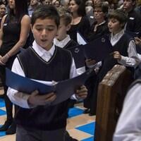 Les Petits Chanteurs chantent lors des funérailles du comédien Paul Buissonneau.