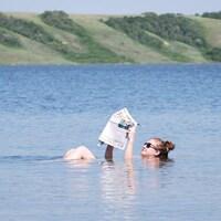 Une femme flotte sue le lac Petit-Manitou en lisant le journal.
