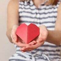 Une femme caucasienne tient un cœur en papier au creux de ses mains.