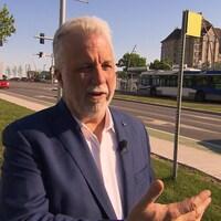 Le premier ministre du Québec, Philippe Couillard, en entrevue devant une rue passante. Un autobus est en arrière-plan.