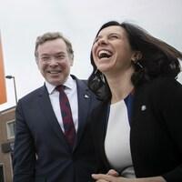 Les deux dirigeants rigolent devant un panneau annonçant la passage de l'autobus 445.