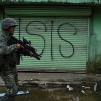 Un soldat philippin patrouille dans une rue de Marawi. Derrière lui, un graffiti sur une porte de garage écrit « ISIS », l'acronyme anglophone du groupe armé État islamique.