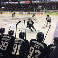 Du banc, des joueurs du Phoenix de Sherbrooke surveillent leurs collègues sur la glace, qui affrontent l'Armada de Blainville-Boisbriand. On les voit de dos.