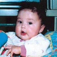 Un bébé aux cheveux ébouriffés dans un siège pour bébés multicolore, avec un jouet coloré entre les mains.