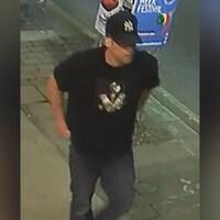 La photo montre un homme avec une casquette noire et un maillot noir qui marche le long d'un trottoir.