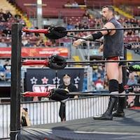 Un lutteur regarde la foule tandis que ses bras sont déposés sur les cordes du ring.