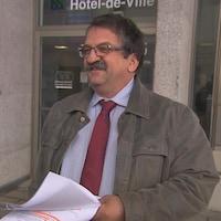 Un homme portant un complet et une moustache sourit aux journalistes devant un édifice.