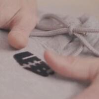 Des mains sur un chandail en coton ouaté.