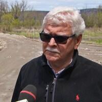 Un homme en entrevue sur un chemin de terre.