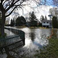 Le secteur des rues de Vimy et Dieppe, dans Pierrefonds-Roxboro, où on voit une rue complètement inondée et des maisons protégées par des digues de sacs de sable, en mai 2017.