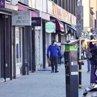 Des personnes masquées marchent sur un trottoir.