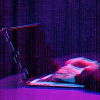 """Une personne travaille sur un ordinateur portable dans une pièce sombre. Il y a un effet """"glitch"""" sur la photo."""