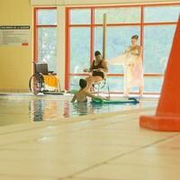 Une femme à mobilité réduite entre dans une piscine avec l'aide d'un lève-personne.