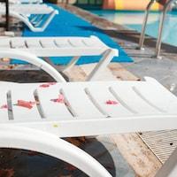 Une piscine vide avec des feuilles sur les chaises.