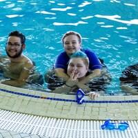 Jordyn Dyck, Jasper Leclaire, Conner Robertson, Alec Schultz et McKenzie Jones-Leibel sont dans l'eau au bord de la piscine en train de sourire devant l'appareil photo.