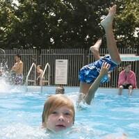 Des enfants se baignent dans une piscine extérieure.