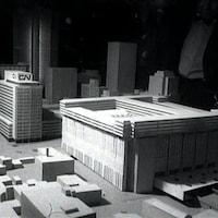 Maquette de la Place Bonaventure et des autres édifices autour avec un homme la regardant en arrière plan.