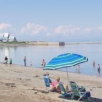Une dizaine de personnes profitent de la plage. Des enfants se baignent tandis que deux femmes se reposent sous un parasol.