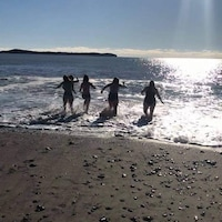 Cinq amies saute dans l'eau de la mer.