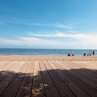 Une plage, avec quelques baigneurs et un soleil radieux