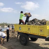 Des personnes ramassent des déchets sur la plage. Deux hommes déversent un contenant plein de détritus dans la benne d'un camion.