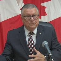 Ralph Goodale est assis à une table, un micro posé devant lui. Il est en train de parler. Derrière lui, trois drapeaux du Canada ont été alignés.