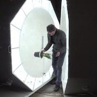 Un chercheur installant une plante dans une imposante machine dégageant une vive lumière blanche.