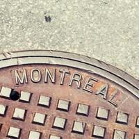 Plan rapproché d'une plaque d'égout portant l'inscription « Montréal ».