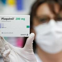 Une personne portant un masque tient une boîte de médicaments.