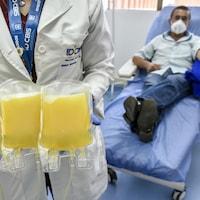 Une femme tient entre ses mains trois sacs de liquide jaune. En arrière-plan, le donateur de ce plasma sanguin est couché sur un lit d'hôpital.