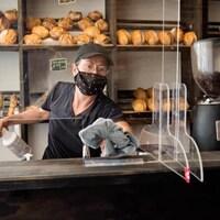 Un panneau de plexiglas devant le comptoir d'une boulangerie.