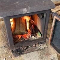 Des bûches flambent dans un poêle en fonte.