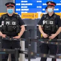Des policiers et des travailleurs au centre de dépistage de la COVID-19 à l'aéroport Pearson de Toronto.