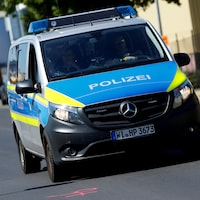 Une véhicule de police allemand roule sur une route.
