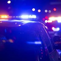 Des gyrophares sont allumés sur une voiture de police, la nuit.