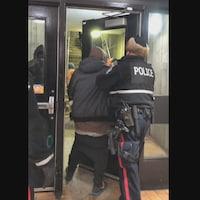Un policier reconduit un homme à travers la porte d'une station de LRT.