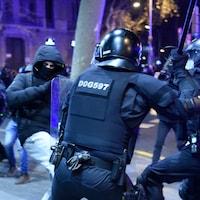 Un manifestant masqué donne un coup de pied aux policiers, qui eux ont leur bâton levé.